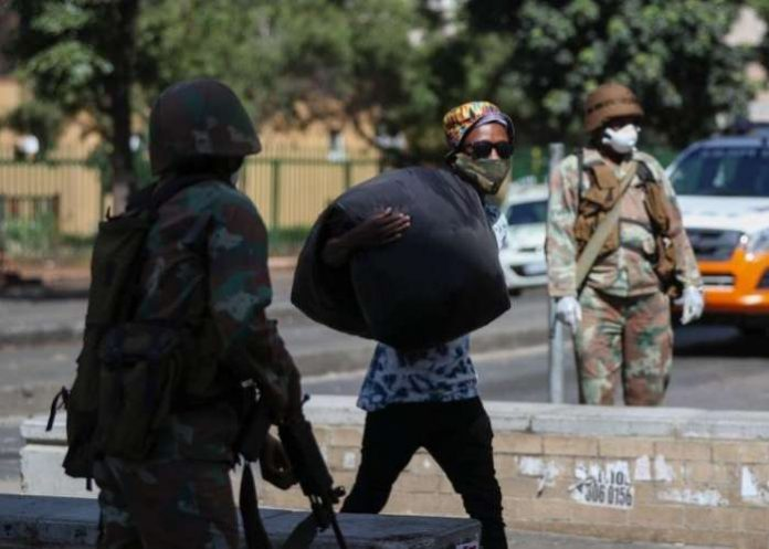 A member of the South African National Defence Forces looks on as a homeless man walks carrying his belongings during the first day of a nationwide lockdown for 21 days to try to contain the coronavirus disease (COVID-19) outbreak, in Johannesburg, South Africa, March 27, 2020. REUTERS/Siphiwe Sibeko